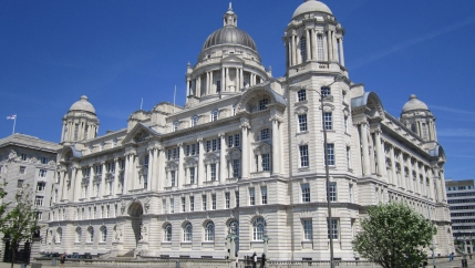 The large white stone facade of the Port of Liverpool building is shown with a silver dome on top.