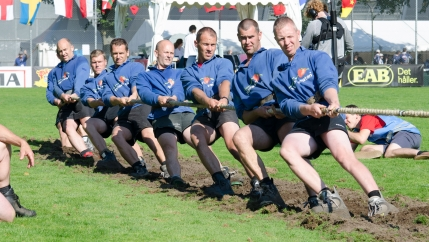 The Belgian men's team wears blue shirts during a tug of war competition.