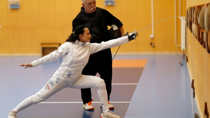Woman in white fencing gear trains with her coach standing behind her wearing black
