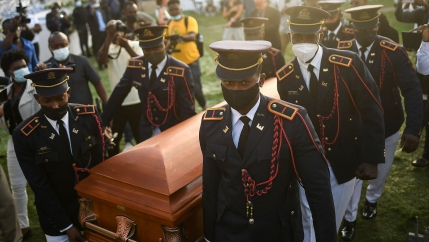 Several men wearing dress military uniforms with service caps are shown carrying a brown wooden coffin.
