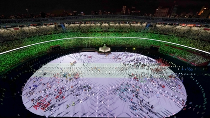 Olympic athletes are shown on the white floor of a large oval stadium shown at night with colorful lighting and mostly empty seats.