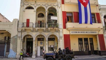 Special forces police patrol the streets as they drive past a large Cuban flag hanging from the facade of a building, in Havana, Cuba