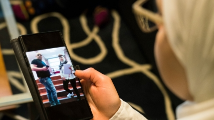 Faeza Satouf, from Syria, looks at a photo of her graduation day on her phone during an interview in Nivaa, Denmark, Wednesday, April 21, 2021.