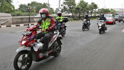 Several people on motorbikes and wearing helmets are shown riding in front of an ambulance.