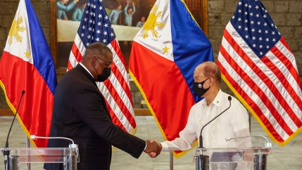 United States Defense Secretary Lloyd Austin and Philippines Defense Secretary Delfin Lorenzana shake hands after a bilateral meeting with their counties' flags behind them