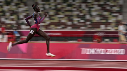 Athing Mu is shown mid-stride on the track in blurred motion.