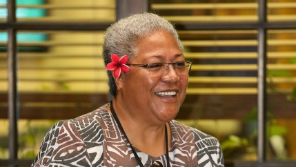 Samoa MP Fiamē Naomi Mata'afa smiles with a red flower in her hair