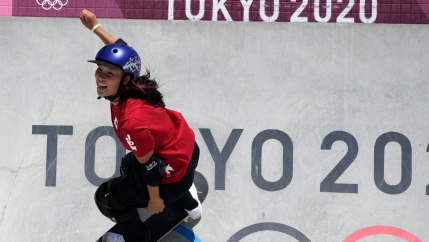 Sakura Yosozumi is shown wearing a red shirt and purple helmet while skateboarding down a wall with