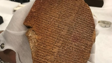 White-gloved hand holds ancient artifact known as the Gilgamesh Dream Tablet.