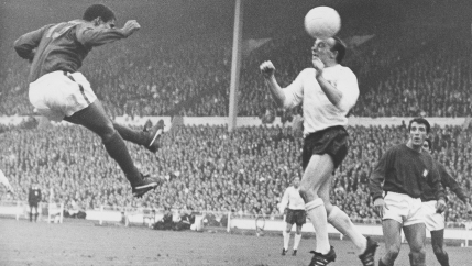Portugal's Eusebio, left, and England's Nobby Stiles have a heading duel for the ball during their World Cup semi-final match at Wembley, London, July 26, 1966.