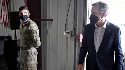 US Secretary of State Antony Blinken is shown looking to his right while walking and wearing a dark face mask with a solider stands in the distance.
