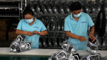 Workers packing ice-skating shoes at a manufacturing factory in the ice and snow sports equipment industry park in Zhangjiakou, in northwestern China's Hebei province, Thursday, July 15, 2021.