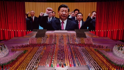 A large auditorium is shown filled with people in color-coordinated clothing with Chinese President Xi Jinping projected on a large screen in the distance.