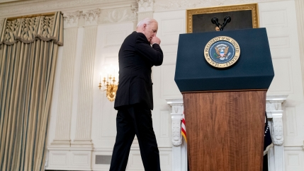 US President Joe Biden is shown wearing a dark suit and walking toward a podium with the President of the United States seal on it.