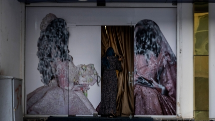 A woman is shown holding back a curtain and entering a salon with painted over pictures of women on either side of the doorway.