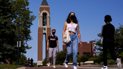 Several people are shown wearing face masks and walking on a college campus with a ornate brick tower in the distance.