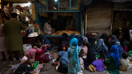 Afghan women and children sit in front of a bakery waiting for bread donations in Kabul's Old City, Afghanistan, on Sept. 16, 2021.