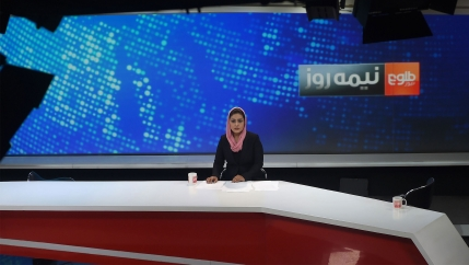 Woman news anchor wearing black outfit and pink headscarf looks into a camera in a Tolo News studio