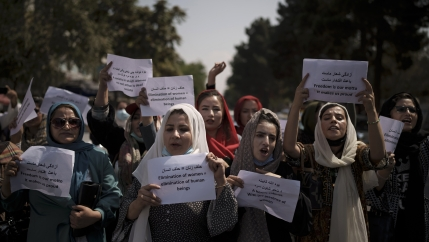 Afghan women march and hold signs in rally