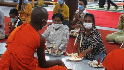 A Buddhist monk, foreground, chants as local residents offer prayer during a ceremony to celebrate Pchum Ben, or Ancestors' Day, at Kob Srov pagoda on the outskirts of Phnom Penh, Cambodia, Sept. 22, 2021. Cambodians on Wednesday began the celebration of
