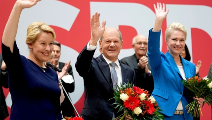 Olaf Scholz is shown wearing a dark suit and standing inbetween two other top German politicians with all three waving their right hands.
