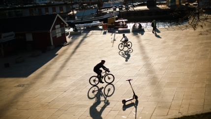 People ride their bicycles at the marina port in Oslo, Norway