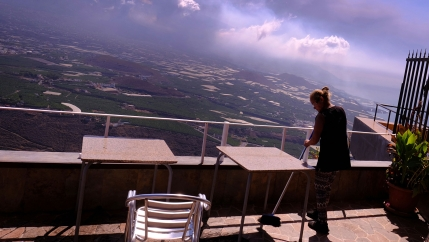 A worker cleans the ash from the tables of a restaurant as lava flows from a volcano on the Canary island of La Palma, Spain on Monday, Oct. 4, 2021.