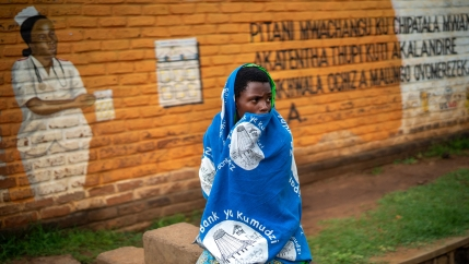 In this Tuesday, Dec. 10, 2019, file photo, a woman waits outside the Migowi Health Clinic to be injected with the world's first vaccine against malaria in a pilot program, in Migowi, Malawi.