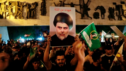 Followers of Muqtada al-Sadr celebrate holding his posters, after the announcement of the results of the parliamentary elections in Tahrir Square, Baghdad, Iraq