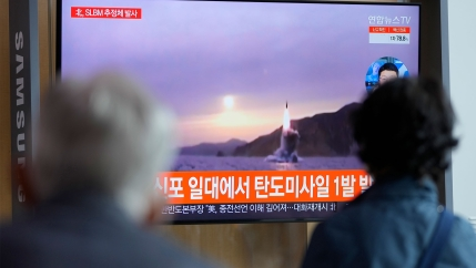 People watch a TV screen showing a news program reporting about North Korea's missile launch with file footage at a train station in Seoul, South Korea