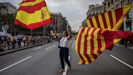 A woman waves flags of Catalonia and Spain as people celebrate a holiday known as