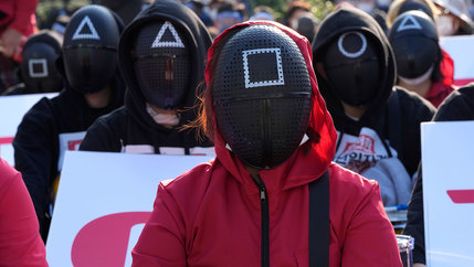 Members of the South Korean Confederation of Trade Unions wearing masks and costumes inspired by the Netflix original Korean series