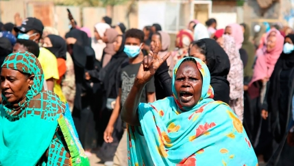 A pro-democracy protester wearing a turquoise blue scarf flashes the victory sign as thousands take to the streets to condemn a takeover by military officials, in Khartoum, Sudan, Oct. 25, 2021.