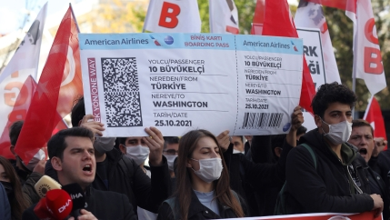Members of a Turkish group hold a symbolic boarding pass for 10 foreignambassadors as they stage a protest near the US Embassy to support Turkey's President Recep Tayyip Erdoğan, in Ankara, Turkey, Monday, Oct. 25, 2021.