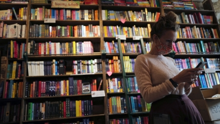 Sylvia Whitman, proprietor of the English and American literature Shakespeare and Co. bookstore, checks her messages on her phone in Paris, France, Thursday, Nov. 5, 2020.