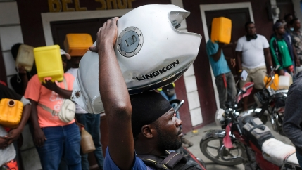 A man balances his motorbike tank on his head as he waits outside a gas station in hopes of filling his tank, in Port-au-Prince, Haiti, on Oct. 23, 2021. The ongoing fuel shortage has worsened, with demonstrators blocking roads and burning tires in Haiti'