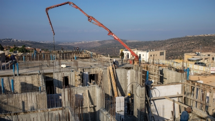 Palestinian laborers work building new houses in the West Bank Jewish settlement of Bruchin near the Palestinian town of Nablus