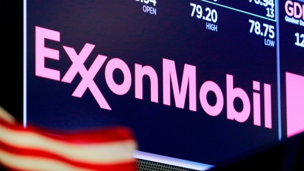 The logo for ExxonMobil appears above a trading post on the floor of the New York Stock Exchange