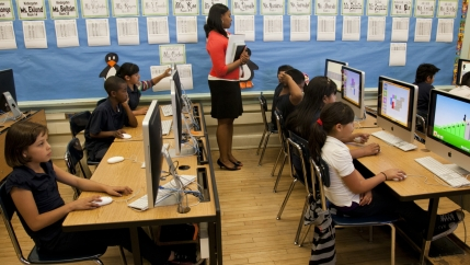 Elementary students sit in a computer lab at school