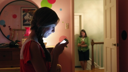 A woman sits on a bed using her phone with another woman in the hallway doing the same