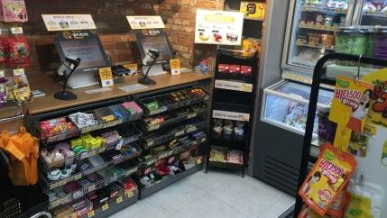 Two computers with scanners are set up on a counter in a convenience store, surrounded by packaged snacks and rows of gum and mints.