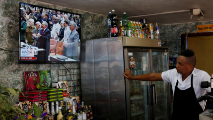 Cuba's President Raul Castro (C) and First Vice-President Miguel Díaz-Canel (R) are seen on a TV screen inside a restaurant during a session of the National Assembly in Havana, Cuba, April 18, 2018. Díaz-Canel became Cuba's president on Wednesday.