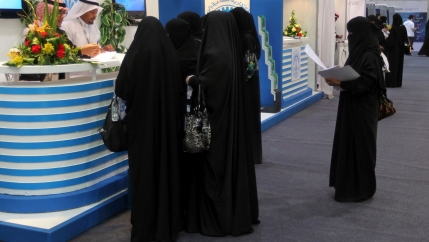 Saudi Arabian women, seeking a job, talk with recruiters during a job fair in Riyadh.