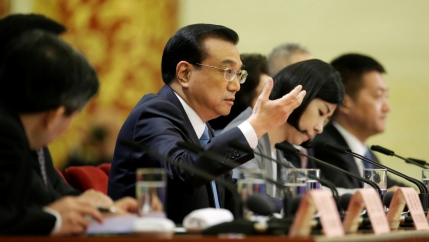 Chinese Premier Li Keqiang speaks at a table lined with microphones during a news conference in Beijing.