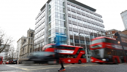 People walk past in a blur the building housing the offices of Cambridge Analytica in central London.