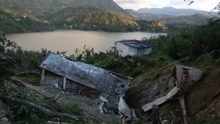 collapsed house in ravine with lake and mountains in background