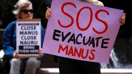 "A pink sign reading ""SOS EVACUATE MANUS"" is held up by a protester."