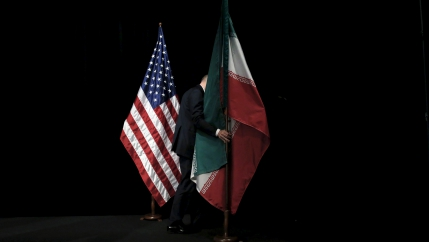 A staff member removes the Iranian flag from the stage after a group picture with foreign ministers and representatives at the Vienna International Center in Vienna, Austria July 14, 2015.
