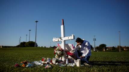 Joe Zevuloni mourns in front of a cross placed in a park to commemorate the victims of the shooting at Marjory Stoneman Douglas High School, in Parkland, Florida, Feb. 16, 2018.