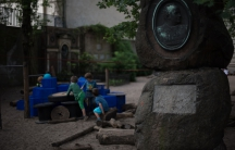 Children climb on a construction near a gravestone in the playground of the Sophienkirche day-care center in Berlin, Germany. The day-care is located on the grounds of the Sophienkirche church, and it's playground occupies a space that was once the parish